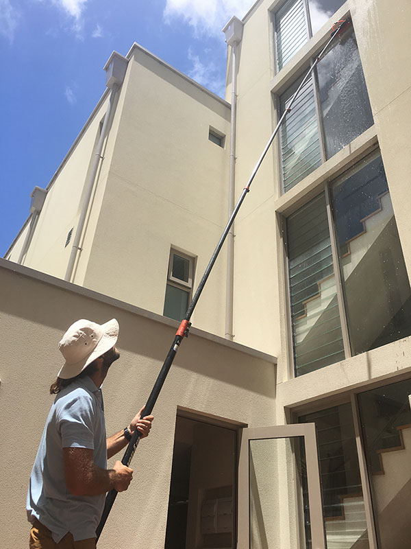 cleaning windows with extendable pole brush